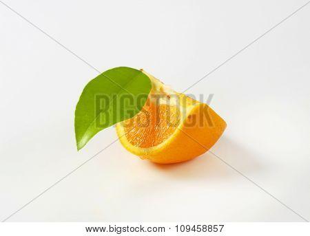 slice of fresh orange with leaf on white background