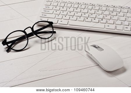 White Slim Keyboard With A White Slim Mouse And Glasses
