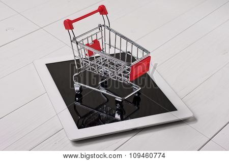 Small Shopping Cart On A White Tablet Computer