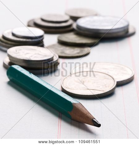 pencil on math paper with coins behind