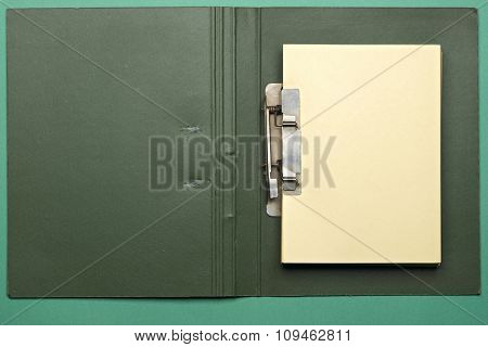 green notebook with yellow pages on green
