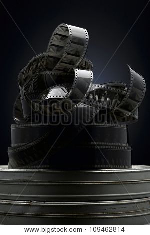 scrambled film reels on canisters against dark background