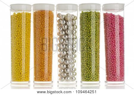 containers of cake decorative sprinkles on white