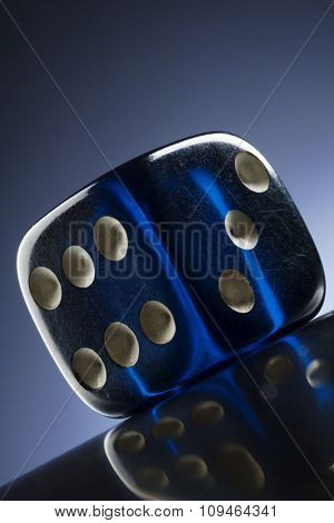 a transparent blue dice on dark blue background