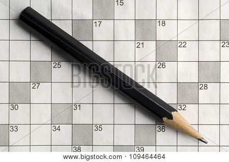 an empty crossword puzzle with a black pencil on it