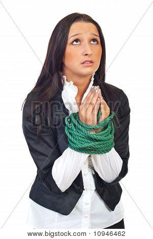 Mulher Executiva com mãos amarradas orando