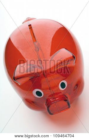 a red transparent piggy bank on white