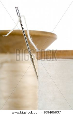 closeup of two spools of thread with the needle stuck in one - focus on the eye of the needle