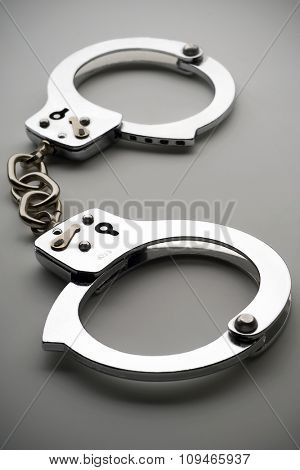 a pair of metal handcuffs on gray surface