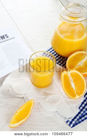 Newspaper with oranges and juice on blue checkered napkin