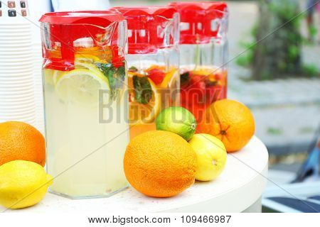 Full jugs with drinks and fruits on table close up