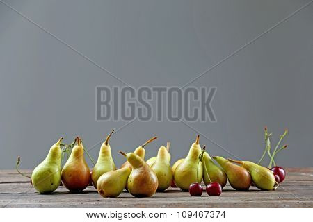 Ripe pears and cherries on gray background