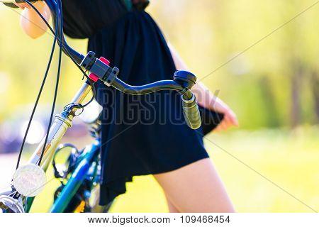 Slim girl in short  dress and bike in park