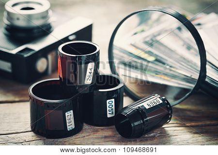 Photo Film Rolls, Retro Camera, Stack Of Photos And Magnifier Closeup