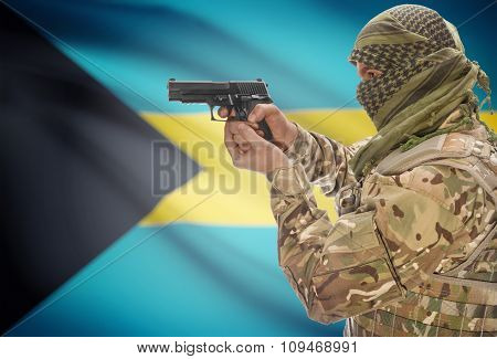 Male With Gun In Hand And National Flag On Background - Bahamas