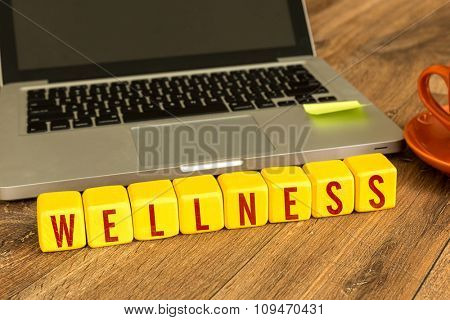 Wellness written on a wooden cube in a office desk
