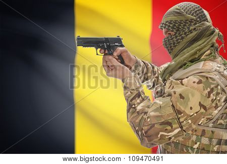 Male With Gun In Hand And National Flag On Background - Belgium