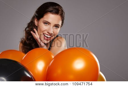woman posing with balloons. Girl smiling , looking at camera.