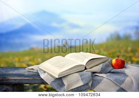 Open book on old wooden bench in mountains