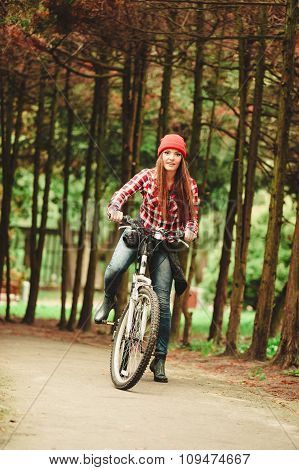 Girl Relaxing In Autumnal Park With Bicycle.