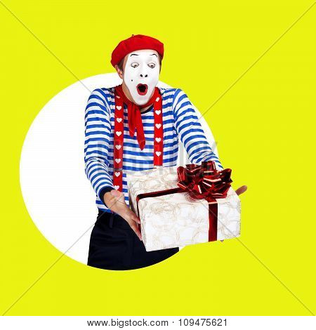 Surprised mime with present.Funny actor in red beret, sailor suit poses on color background