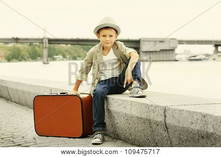 Little boy with suitcase on the riverside