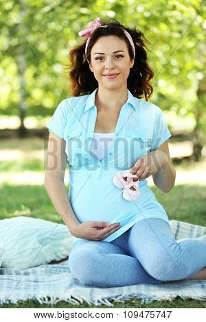 Cute happy pregnant woman with baby booties on white blanket in the park