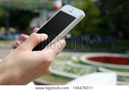 Female hand holding smart mobile phone outdoors
