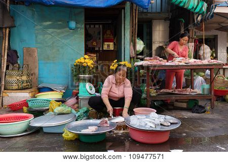 HO CHI MINH VILLE, VIETNAM, FEBRUARY 26, 2015 : A woman is selling fishes in the street at the Cho Binh Tay market in the Chinatown district of Ho Chi Minh Ville, (Saigon), Vietnam.