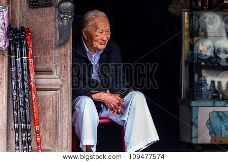 HOI AN, VIETNAM, DECEMBER 14, 2014 : A senior seller is sitting in front of his handicraft souvenir shop in the city of  Hoi An, Vietnam