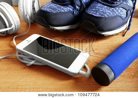 Sport shoes, equipment and smart phone with headphones on light background