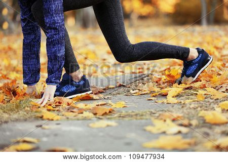 Woman in sportswear and sneakers in park