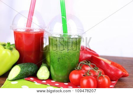 Fresh vegetable juices in plastic cups on wooden table, on light background