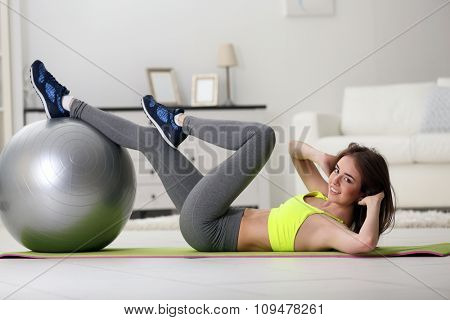 Beautiful young girl doing exercises with fit ball at home