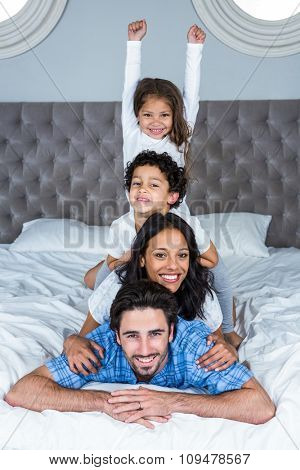 Happy family on the bed posing for camera