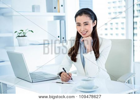 Smiling businesswoman writing on clipboard at the desk in work