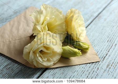 White eustoma in envelope on wooden background