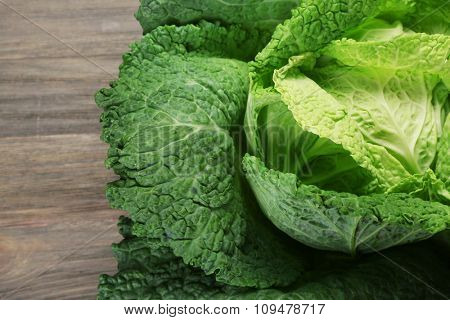 Savoy cabbage on wooden background, close up