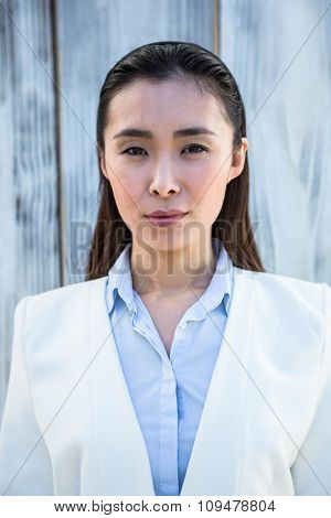 Portrait of Asian businesswoman against wooden background