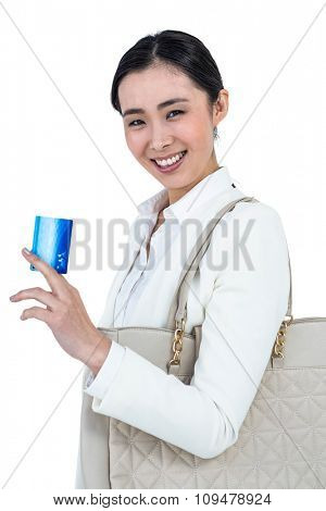 Smiling woman with a credit card in hand against white background