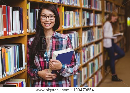 Smiling student leaning against bookshelves holding book at the university