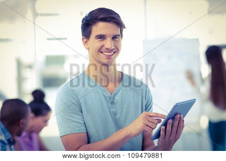 Young creative worker using tablet in casual office