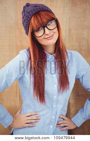 Smiling hipster woman with hands on hips against wooden background