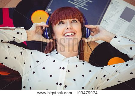Smiling hipster woman with headphones listening to music on the floor