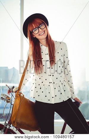 Smiling hipster woman with her bicycle in a bright room