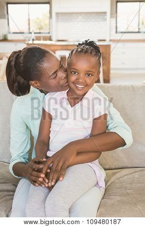 Loving mother with daughter on the couch in living room