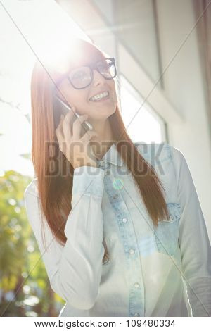 Smiling businesswoman using her smart phone outside