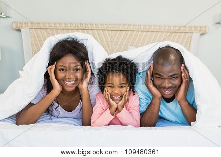 Happy family lying on bed at home