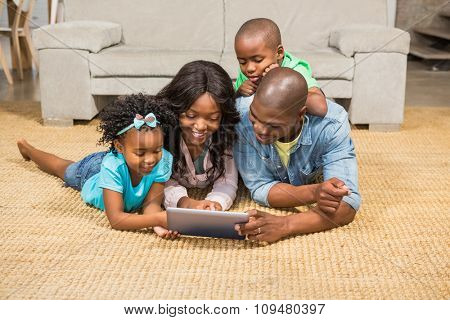 Happy family lying on the floor using tablet in the living room