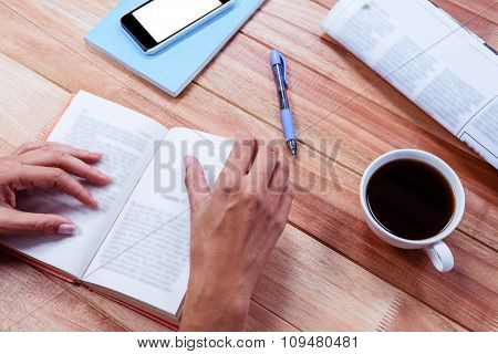 Overhead of feminine hands holding a book with coffee, newspaper and smartphone on table